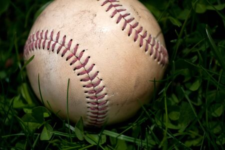 Closeup of an aged and worn hardball or baseball laying in the green grass. Shallow depth of field. photo