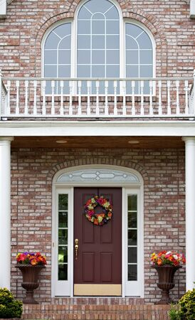 The front entrance of a large custom built luxury home in a residential neighborhood.  photo