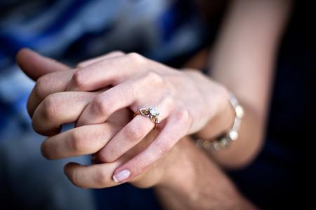 ring engagement: Close up de una manos de parejas j�venes y anillo de compromiso con acentos de platino y oro de diamantes. Profundidad de campo.