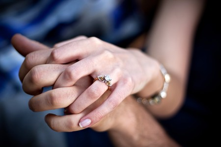 engagement: Close up of a young couples hands and diamond engagement ring with platinum and gold accents. Shallow depth of field.