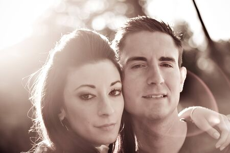 A good looking young couple posing together.  Backlit lighting with strong lens flare and sepia tone.  Imagens