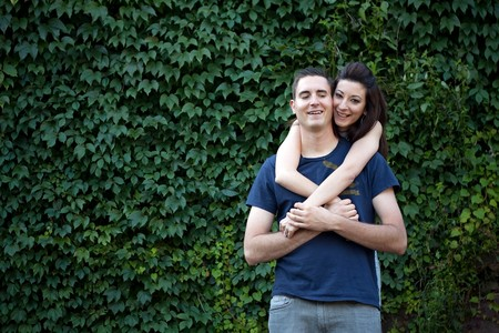 ivy wall: A happy young couple in their mid 20s together outdoors in front of some green ivy.