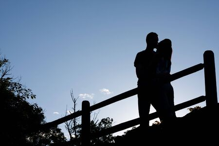 romantically: Silhouette of an affectionate couple romantically kissing each other in the early evening hours.