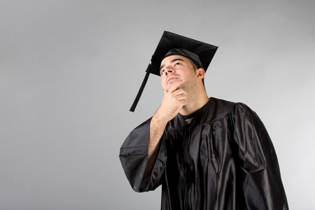A recent college or high school graduate in his cap and gown thinking and looking contemplative. photo