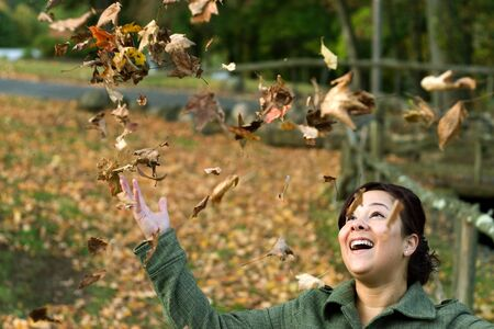 A pretty young woman laughing as the leaves fall all around her during the autumn season. photo