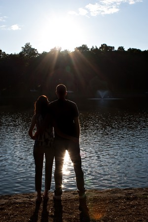 Silhouette of an affectionate couple embracing each other in the early evening hours with back lit lighting. photo
