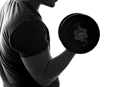 levantando pesas: Silueta iluminado espalda de un hombre joven, levantamiento de pesas en blanco y negro.
