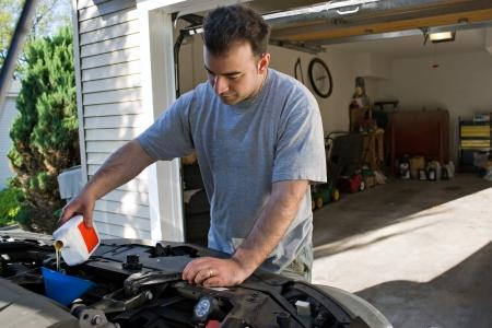 오일 교환의 끝에서 자신의 자동차 엔진 오일을 추가하는 젊은 남자.