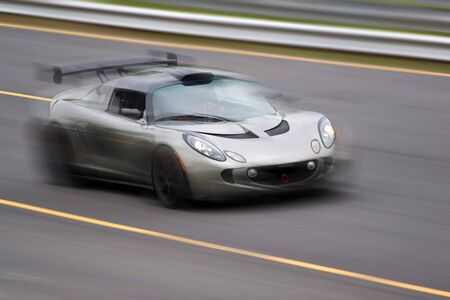 A fast silver sports car speeding down the road.  Slight motion blur.