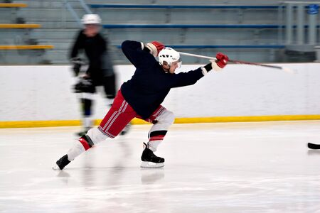 A hockey player shooting the puck as he speeds down the ice.  Slight motion blur. Stock Photo - 7412147