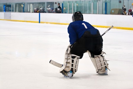 A hockey goalie awaiting the return of the puck so he can resume his defensive role.  Shallow depth of field. Stock Photo