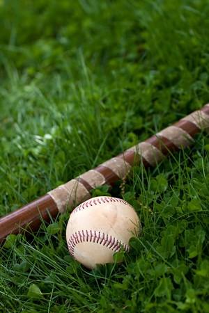 An old wooden baseball bat and ball laying in the green grass with copyspace.  Shallow depth of field. photo