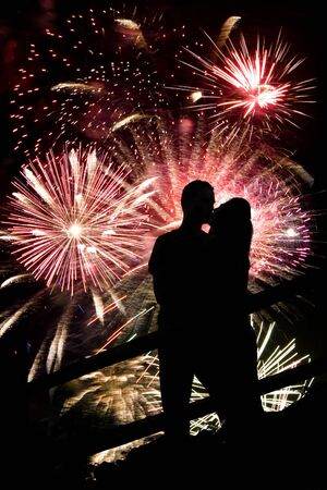 new love: A silhouette of a kissing couple in front of a huge fireworks display.