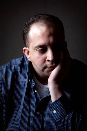 contemplative: A middle aged man with a contemplative look on his face.  He could be worried or depressed about something.