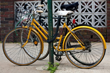 city bike: A couple of bicycles chained to a post in the city. Stock Photo
