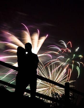 verlobt: Eine Silhouette eines kissing Paares an einem riesigen Feuerwerk.