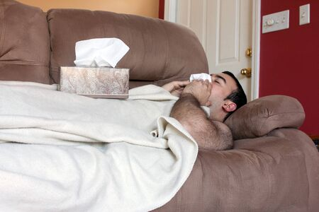recuperating: A young adult sick on the couch at home blows his nose with a tissue.