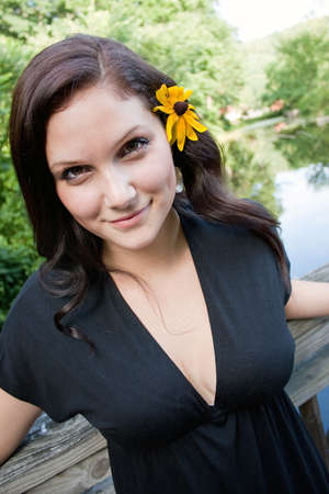 A beautiful young brunette woman wearing a black eyed susan wildflower in her hair. Stock Photo - 7474588