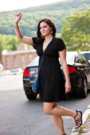 A gorgeous brunette woman hails a cab at the side of the road in the city. photo
