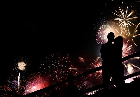 A silhouette of a kissing couple in front of a huge fireworks display. photo