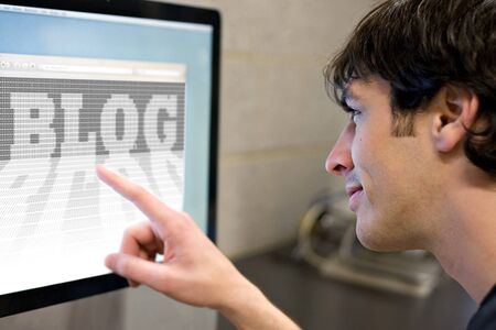 A young main pointing at a computer screen that reads BLOG in the web browser window.   photo