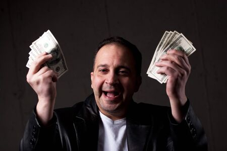 A man celebrating holding handfuls of green American cash money. Shallow depth of field with focus on the face. photo