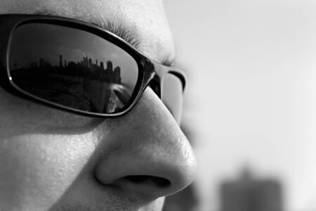tough man: Close up of a man wearing sunglasses with the New York City skyline reflecting in the lens. Shallow depth of field. Stock Photo