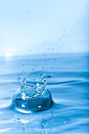 Een achtergrond structuur van blauwe water en plons met druppels die een kroon vormen. Ondiepe scherptediepte.  Stockfoto