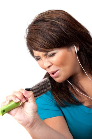 A Hispanic woman listening to music playing through her stereo earbud headphones and pretending to sing on a microphone that is actually a hair brush.  photo