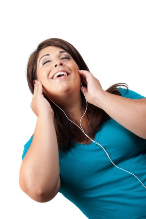 An attractive Hispanic woman listening to and getting into the music playing through her stereo earbud headphones.  photo