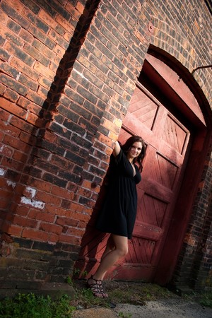 A pretty young woman in a black dress posing in an old doorway.  photo