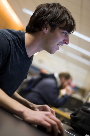 A young man or student using a personal computer happily. photo