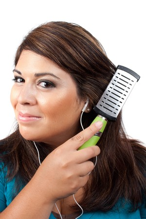 A young brunette woman listening to music while brushing her hair. photo