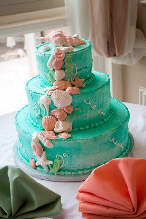 A blue beach themed wedding cake with three tiers. photo