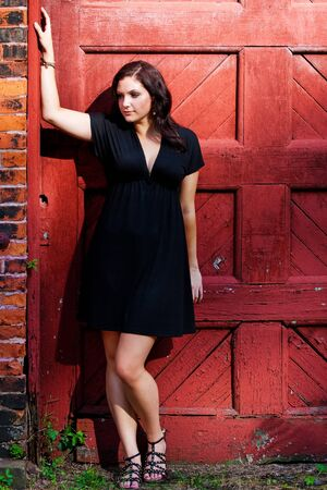 A pretty young woman in a black dress leaning against an old red doorway.  Stock Photo - 7795139