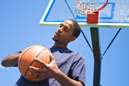 backboard: African American man posing with a basketball beneath the backboard. Stock Photo