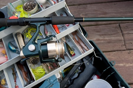 anglers: A fishermans rod reel and tackle box filled with lures and bait ready for the start of fishing season. Stock Photo