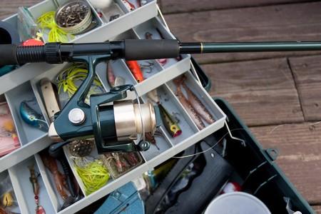 Eine Fishermans Rod Reel und Tackle Box gefüllt mit lockt und Köder bereit für den Start der Fangsaison. Standard-Bild