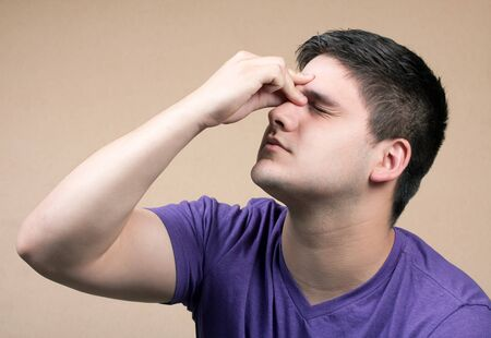 Young man has an intense headache. He might be experiencing stress during a time of economic crisis or other hardship. photo