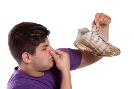 A teenager pinches his nostrils closed over the odor given off from the athletic shoe he is holding. photo