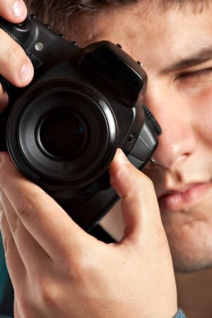 stock photography: A young teenage photographer taking a photo with his DSLR camera. Shallow depth of field.