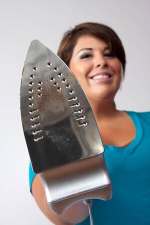 A young woman at home holding up her household iron with a happy grin isolated over a silver background. Reklamní fotografie