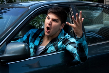 angry: An irritated young man driving a vehicle is expressing his road rage.