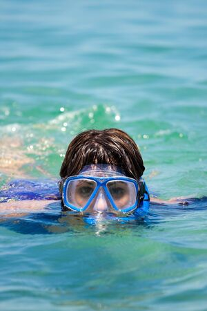 A brunette woman snorkeling in the tropical waters of the Caribbean sea.