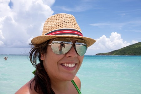 Woman smiles in the tropical Caribbean ocean on the  island of Culebra. Man taking her photo is shown in the reflection of her sunglasses. photo
