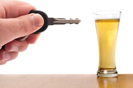 Drunk driving conceptual image with a hand holding some car keys and a glass of beer in the background.  Shallow depth of field. photo
