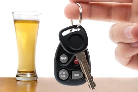 borracha: Bebe imagen conceptual de conducci�n con una mano sosteniendo algunas claves de coche y un vaso de cerveza en segundo plano. Profundidad de campo.