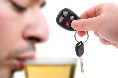 man drinkt bier: Dronken rijden concept met een hand met sommige autosleutels en een man bier drinken op de achtergrond.  Ondiepe diepte van het veld.