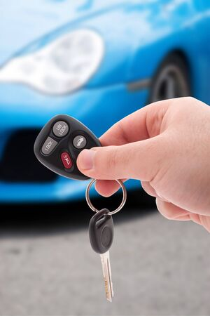 A hand holding car keys and a remote control for keyless entry. Stockfoto