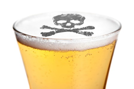 The dangers of alcoholism concept with a skull and cross bones symbol floating on top of the beer.
